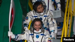 Japanese astronaut Koichi Wakata (top) and Russian cosmonaut Mikhail Tyurin, board the Soyuz TMA-11M spacecraft with the torch of the 2014 Sochi Winter Olympic Games at the Baikonur cosmodrome on November 7.