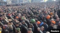 People cheer as they listen to police officers from Lviv who have joined the antigovernment protests during a rally on Independence Square in Kyiv on February 21.
