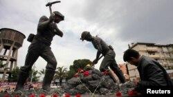 Люди возлагают цветы к памятнику шахтерам в городе Сома на западе Турции