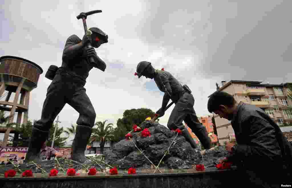 Цветы у монумента шахтерам в центре города Сома в Турции.