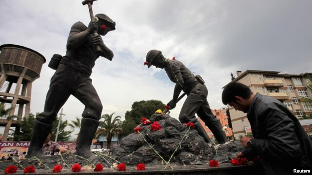 A man lays carnations at the Miners Monument in central Soma, a district in Turkey's western province of Manisa, on May 14.
