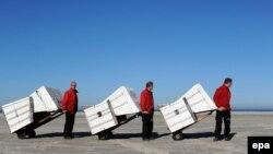 Туристік фирма қызметкерлері жағалаудағы орындықтарды жинап әкетіп барады. Германия, Санкт-Петер-Ординг, 12 наурыз 2014 жыл. (Көрнекі сурет)