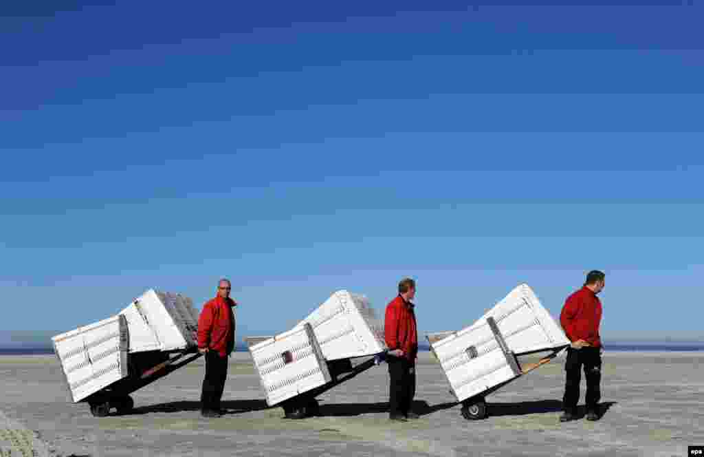 Staff members of the local tourist office transport deckchairs to the North Sea beach of St.Peter-Ording, Germany, on March 12. (epa/Karsten Rehder)