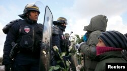 """Pamje e mëparshme e policëve dhe migrantëve në kampin e njohur me emrin """"xhungël"""" në Kale të Francës"""