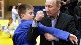 Владимир Путин в бытность премьер-министром России показывает мальчику прием дзюдо. Кемерово, 24 января 2012 года.