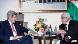 U.S. Secretary of State John Kerry (left) and Palestinian Authority President Mahmud Abbas talk before a meeting at the presidential compound in the West Bank city of Ramallah on January 3.