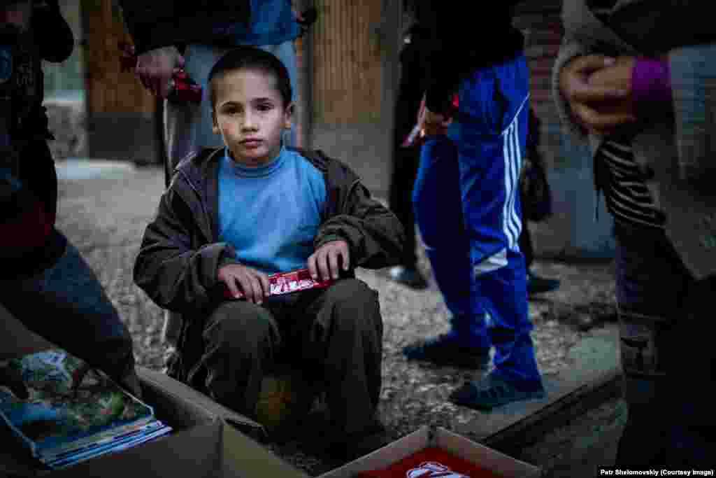 A young refugee boy unwraps chocolate distributed by volunteers in accommodation for displaced Ukrainians in Donetsk. Despite the truce between the separatists and Ukrainian government forces, there is still sporadic fighting. Refugees from shelled areas have sheltered inside Donetsk University campus buildings.