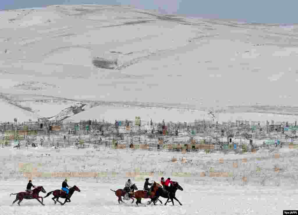 "Kyrgyz riders play the traditional Central Asian sport of Kok-boru, know also as Buzkashi or Ulak Tartis (""goat grabbing""), near the village of Besh-Kungey, some 20 kilometers from Bishkek. (AFP/Vyacheslav Oseledko)"