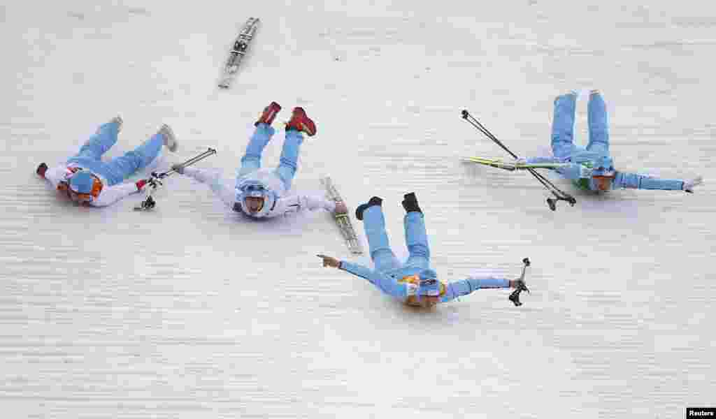Norway's winning team members celebrate by sliding after the flower ceremony for the nordic-combined team event. (Reuters/Michael Dalder)