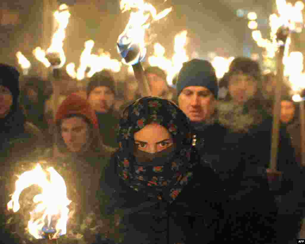 Marchers hold torches during a march in Lviv on January 1, 2016, as they mark the 107th anniversary of the birth of Stepan Bandera, a Ukrainian politician and one of the leaders of Ukrainian national movement in western Ukraine. (AFP/Yuriy Dyachyshyn)