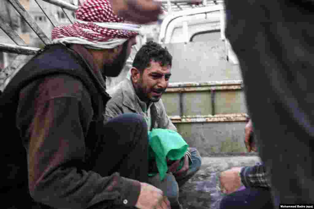 Bashar al-Toum (center) cries as he holds the body of one of his three dead children in a car on the way to the cemetery in the Syrian city of Douma.  At least 13 were killed, including six children, due to bombing on the rebel-held city. (epa/Mohammed Badra)
