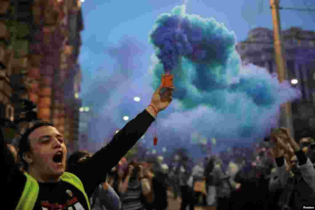 Пратэстовец запальвае паходню падчас акцыі пратэсту супраць ураду прэм'ер-міністра Аляксандра Вучыча ў Бялградзе, Сэрбія.