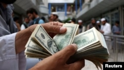 A money changer counts U.S. dollar banknotes at money change market in Herat province, Afghanistan June 3, 2018. Picture taken June 3, 2018. REUTERS/Jalil Ahmad