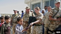British and Romanian soldiers from the NATO-led force distribute school bags to Afghan children on the outskirts of Kabul.