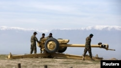 Afghan National Army (ANA) soldiers clean an artillery at the hilltop in Central Afghanistan.