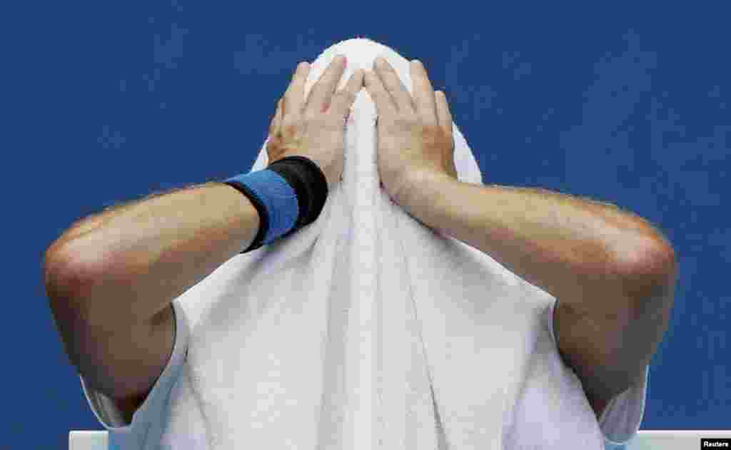 Ernests Gulbis of Lativa holds a towel over his head during a break in play in his men's singles match against Sam Querrey of the United States on January 15.