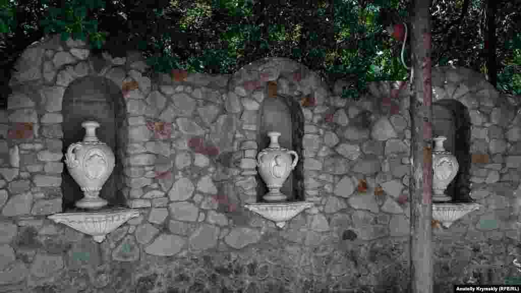 Каменная стена с кувшинами в античном стиле