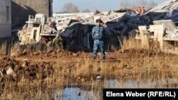 """""""Бесоба"""" тұрғын үй кешеніндегі құлаған көп қабатты үйді күзетіп тұрған полиция қызметкері. Қарағанды, 7 сәуір 2012 жыл."""