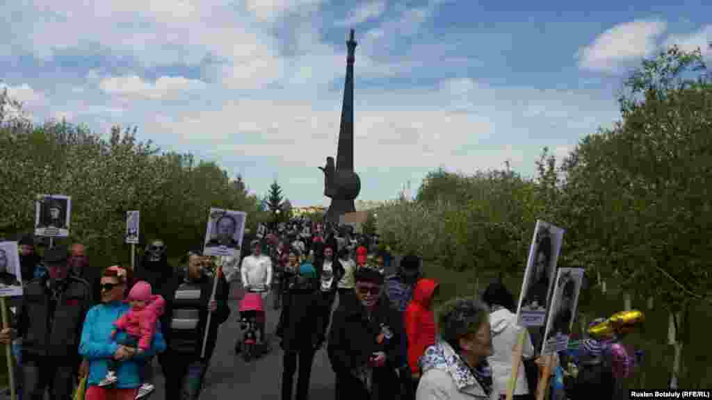 «Мәңгілік полк» шеруіне қатысушылар Астанадағы «Отан қорғаушылар» ескерткіші жанынан өтіп барады.