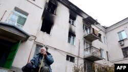 Ukraine -- An elderly man sits in front building destroyed during combat and shelling between Ukrainian forces and pro-Russian militants in eastern city of Donetsk, 13, 2014