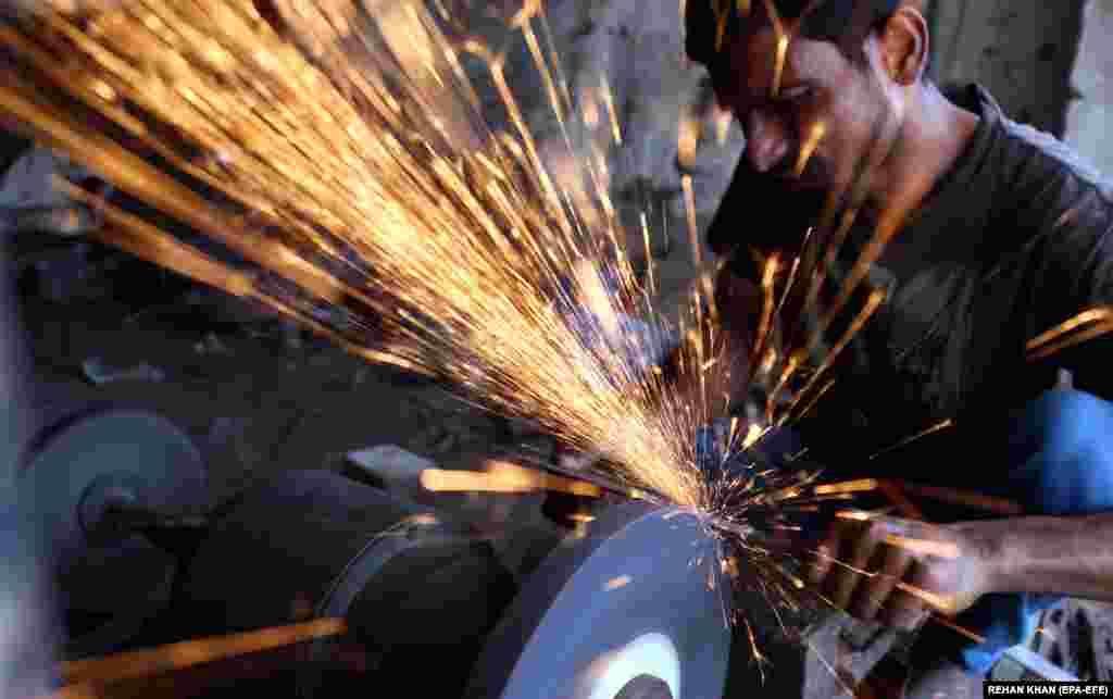 Кузнец точит ножи перед мусульманским праздником Курбан-байрам в Карачи, Пакистан