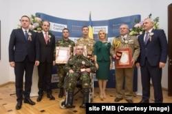 Politicieni în jurul militarilor răniți. Primăria Capitalei le-a oferit diplome și distincții. În centru: caporalul Pătru Eugen Valentin