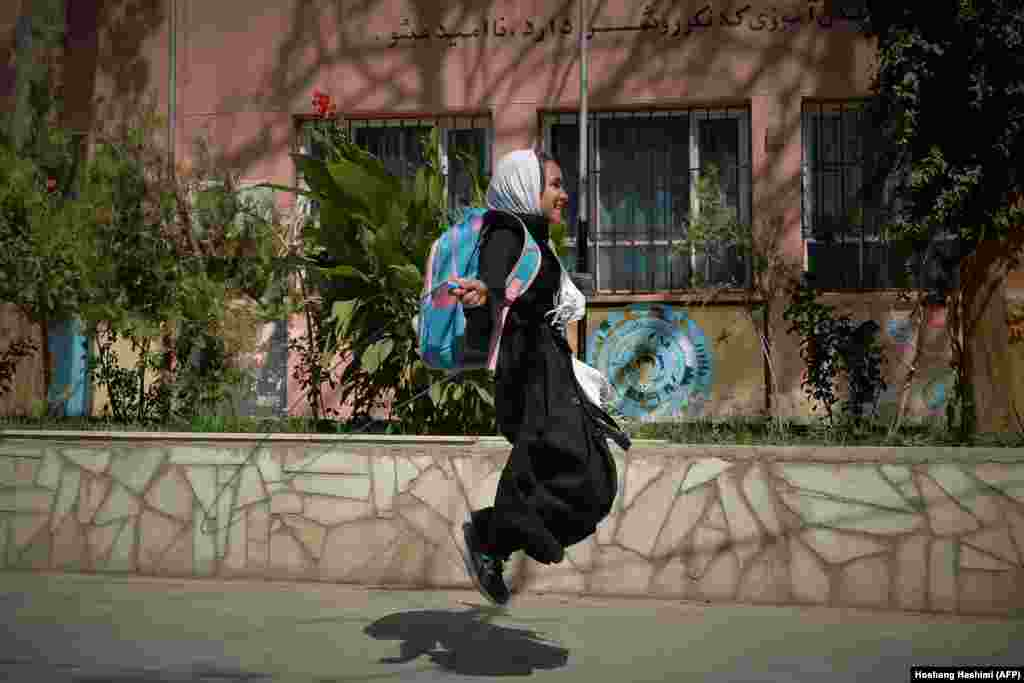 A young Afghan student jumps over her skipping rope outside a school in Herat on September 20.