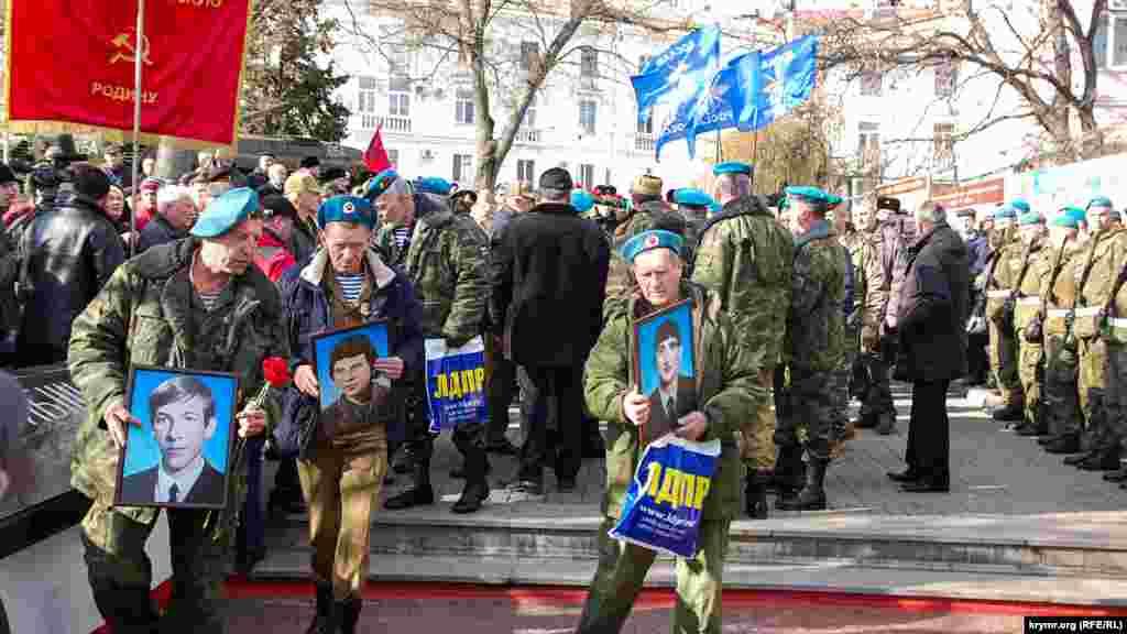 Ветерани війни з портретами загиблих солдатів і пакетами з рекламою російської партії ЛДПР