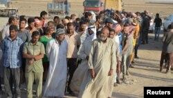 Жители селений в Ираке, которые были вынуждены покинуть свои дома, спасаясь от экстремистской группировки «Исламское государство» (ИГ), стоят у контрольно-пропускного пункта возле Багдада. 10 июля 2016 года.