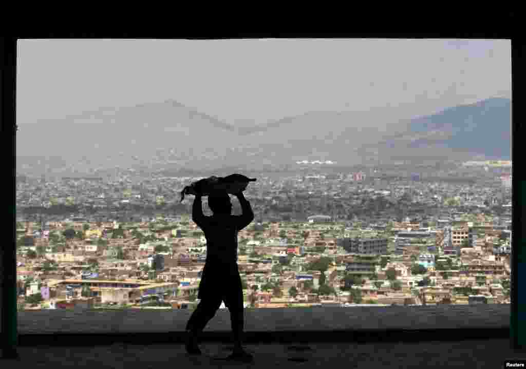 A boy carries bread to sell on a hilltop overlooking Kabul. (Reuters/Mohammad Ismail)