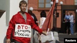 A lone anti-WTO protester distributes leaflets outside the State Duma in Moscow on July 10.