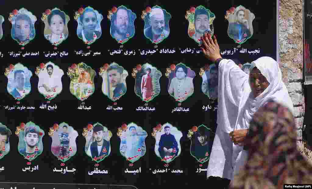 An Afghan woman cries as she touches a banner displaying photographs of victims of a wedding hall bombing during a memorial service in Kabul. The bombing killed at least 80 people. A local affiliate of the Islamic State extremist group claimed responsibility for the attack. (AP/Rafiq Maqbool)