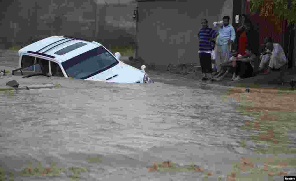 A family waits for rescue workers after their vehicle was submerged in flood waters on the outskirts of Karachi.