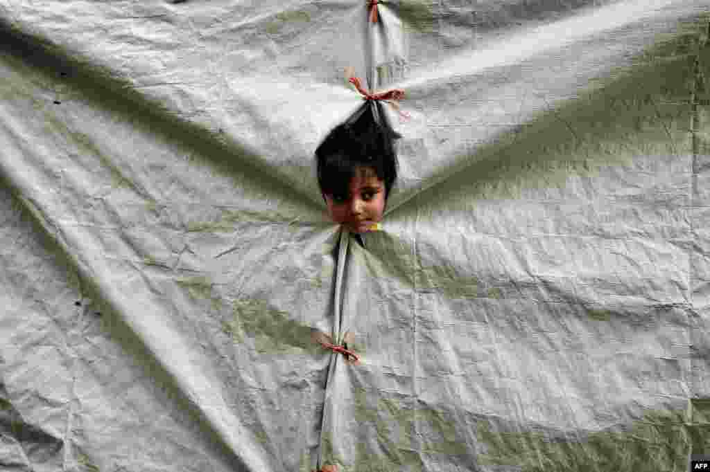 A child peers out of her tent at a refugee camp on the Greek island of Chios. (AFP/Louisa Goulimaki)