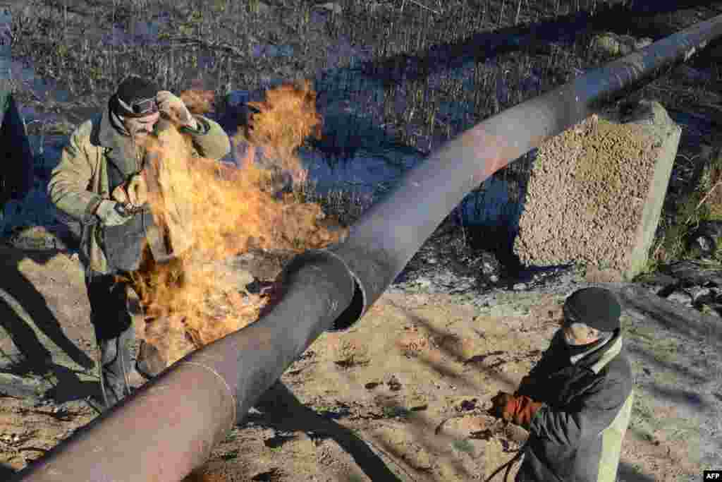 Workers repair a gas pipeline damaged during shelling between Ukrainian forces and pro-Russian militants in the eastern village of Krasnyi Pakhar, in the Donetsk region. (AFP/Aleksandr Khudoteply)