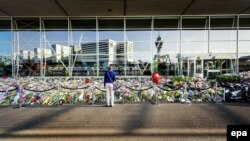 The Netherlands -- A sympathizer stands in front of a sea of flowers left in memory of the victims of Malaysian Airlines flight MH17, at Schiphol Airport, near Amsterdam, The Netherlands, July 31, 2014.