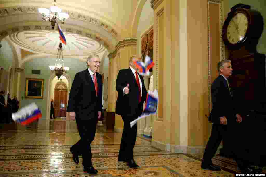"Small Russian flags bearing the word ""Trump"" are thrown by a protester toward U.S. President Donald Trump, as he walks with Senate Majority Leader Mitch McConnell in Washington on October 24. (Reuters/Joshua Roberts)"