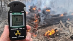 A Geiger counter shows increased radiation levels as a forest fire burns in the exclusion zone around the Chernobyl nuclear power plant on April 5.