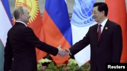 Chinese President Hu Jintao (right) greets his Russian counterpart Vladimir Putin in Beijing