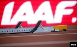 Стартовая колодка бегунов на фоне логотипа Международной федерации легкой атлетики