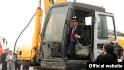Президент Таджикистана Эмомали Рахмон управляет трактором на церемонии начала строительства мечети. 5 октября 2011 года.