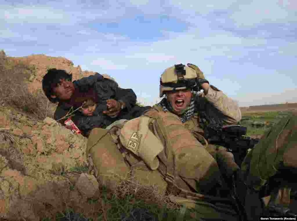 A U.S. marine takes cover with Afghan civilians during a firefight with Taliban militants in 2010. The Taliban have been fighting a sputtering insurgency in Afghanistan since the foreign troops arrived.