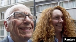 News Corporation CEO Rupert Murdoch leaves his flat with Rebekah Brooks, chief executive of News International, in central London on July 10.
