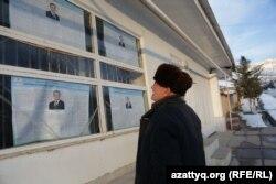 Мужчина читает информацию на предвыборных плакатах в селе Ташкентской области. 27 ноября 2016 года.