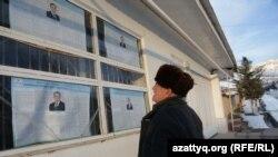 Житель Ташкентской области читает на плакатах информацию о кандидатах в президенты Узбекистана.