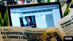 Russia -- A traveller with a laptop computer and a newspaper reads news reports about the arrival of former CIA agent Edward Snowden to Russia, at Moscow's Sheremetyevo Airport, 24Jun2013
