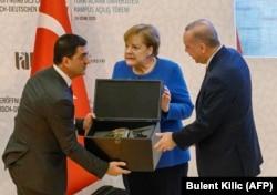 Ангела Меркель (в центре) в Турции встречалась с Реджепом Эрдоганом (справа) совсем недавно, в конце января. Но с тех пор многое изменилось