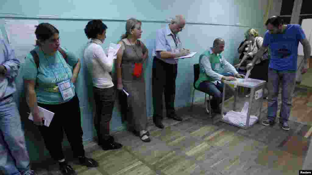 Observers line up in front of a wall, while a voter casts his ballot, at a polling station in Tbilisi.