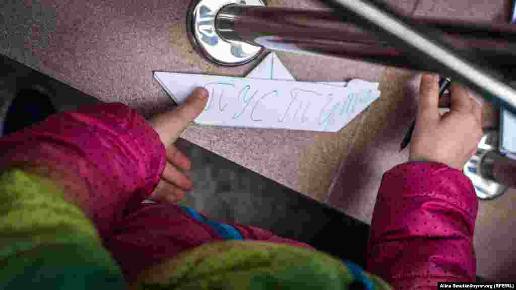 Сафіє Куку, дочка заарештованого ялтинця Емір-Усеїна Куку, підписує для суддів паперовий кораблик. Сімферополь, 20 жовтня 2017 року