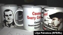 Кружки для продажу на благодійному заході з портретами політв'язнів Олександра Кольченко та Олега Сенцова